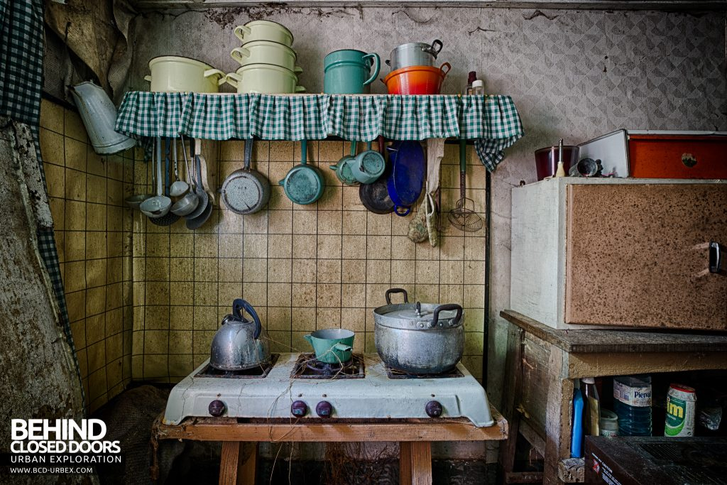 Little Green House - Utensils hang above a rickety stove in the kitchen