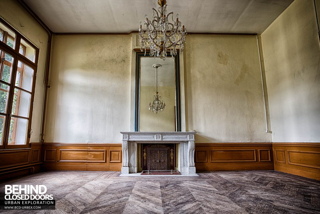 Chateau de la Chapelle - Wider view of the room with fireplace and mirror, with chandelier above