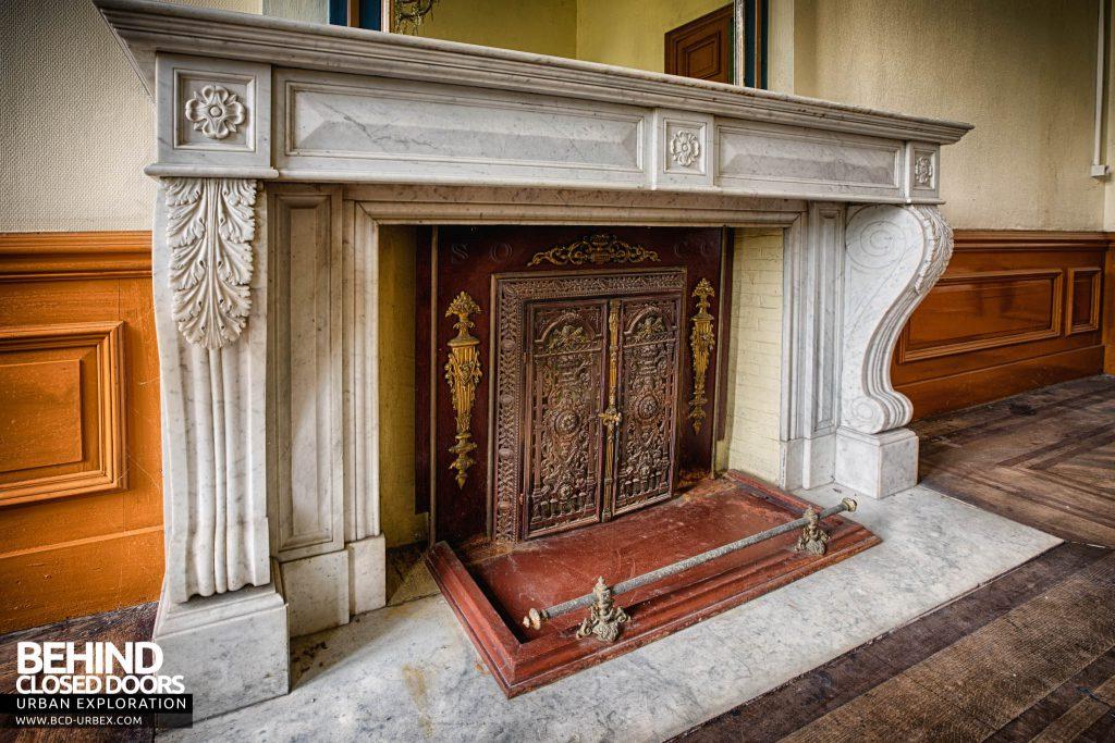 Chateau de la Chapelle - Fireplace detail with ornate fire-guard doors