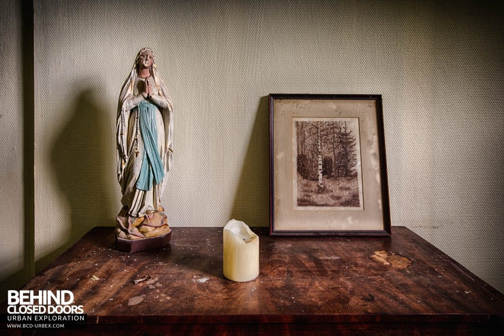 Chateau de la Chapelle - Side table with religious figure, candle and picture