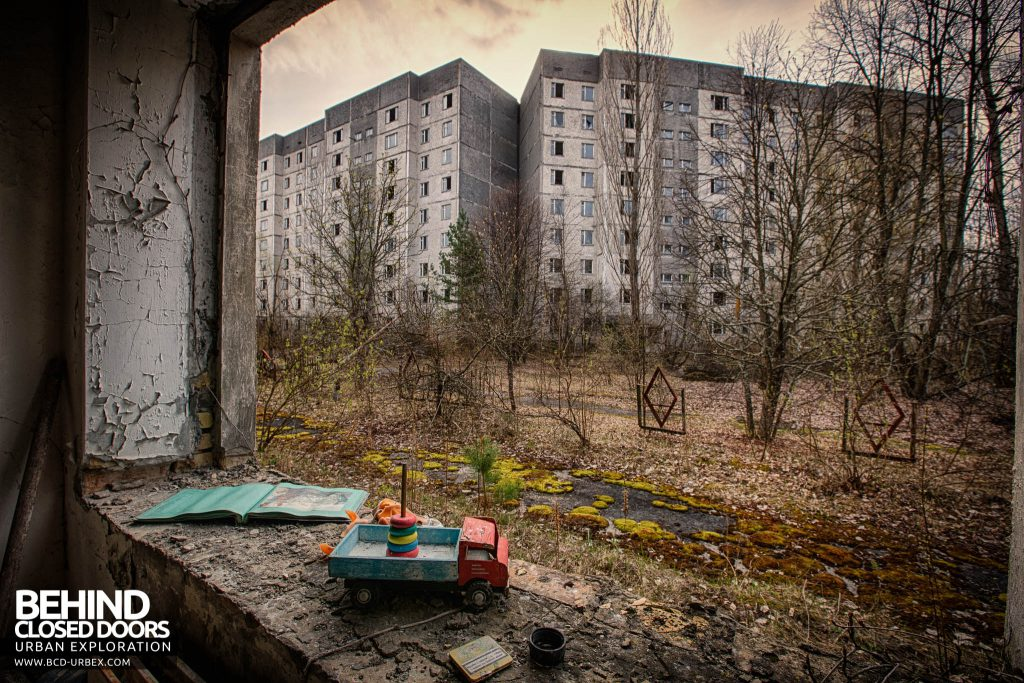 Pripyat Schools and Nurseries - Toy in window with tower blocks behind