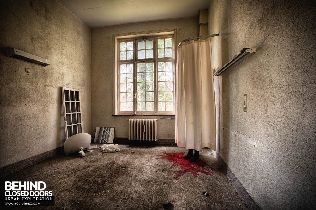 Salve Mater Psychiatric Hospital - A room with boots behind a shower curtain, surrounded by paint resembling blood