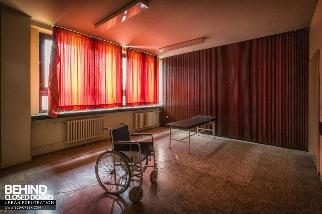 Psychiatrie V Germany - Wheelchair in room with red curtains