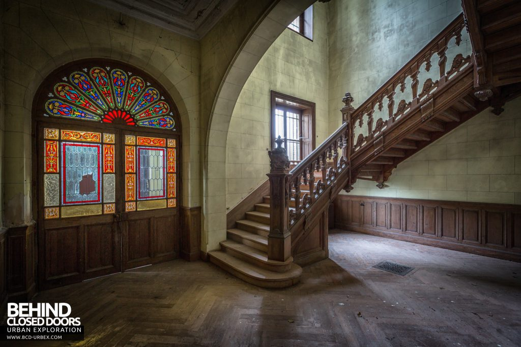 Château Poseidon, France - Staircase and stained glass windows in the front doors