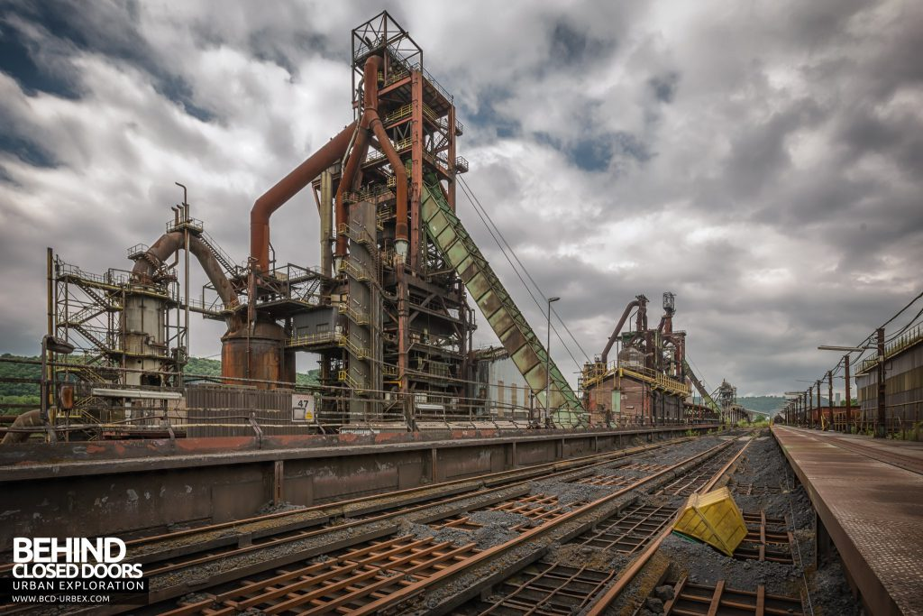 Florange Steelworks, France - Track over the coal and iron ore hoppers with blast furnaces behind