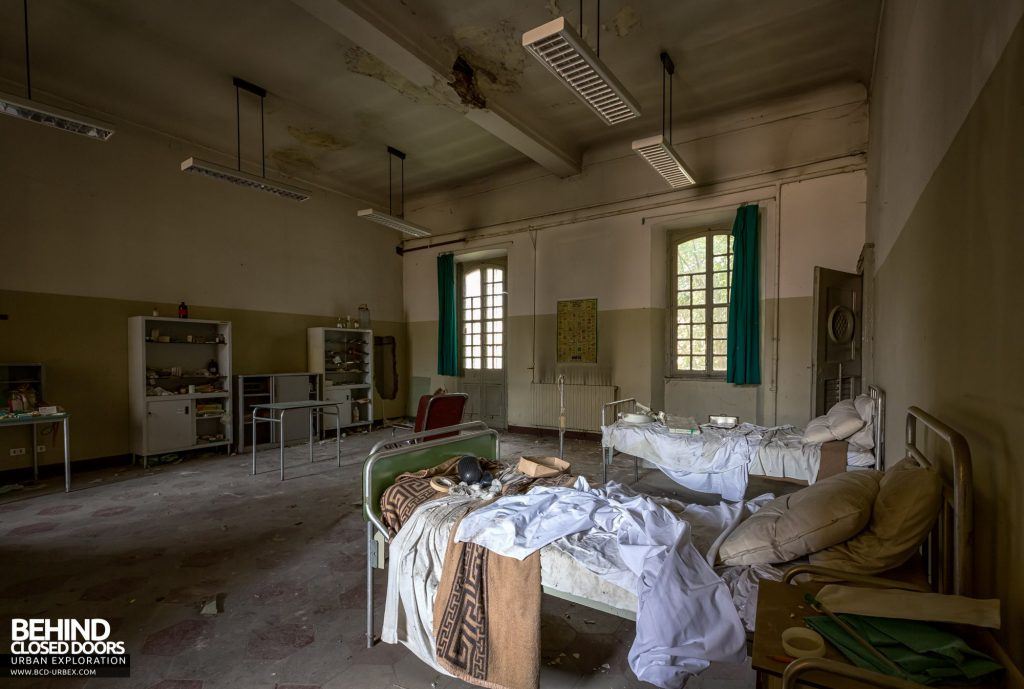 Manicomio Di Voghera - Fully stocked bedroom with beds, a wheel chair and cupboards of medical items