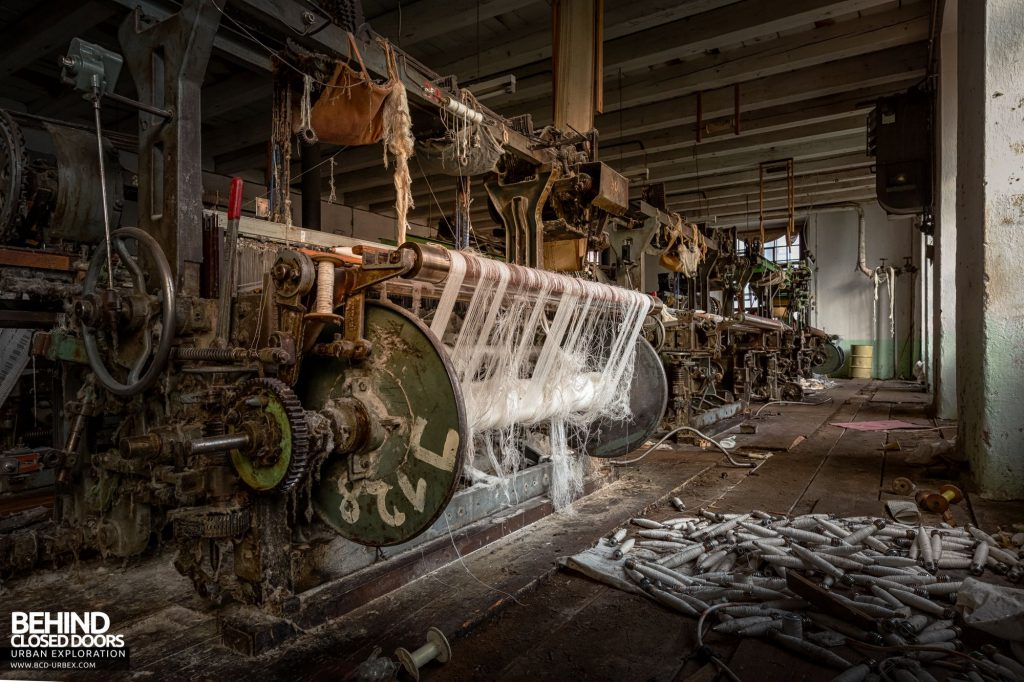 Anderl Textile Mill - Pile of bobbins next to weaving machine