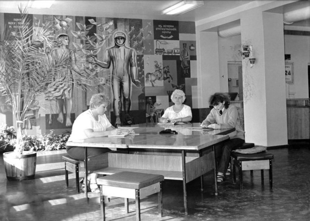 A group of ladies in the post office, with the panting on the wall behind